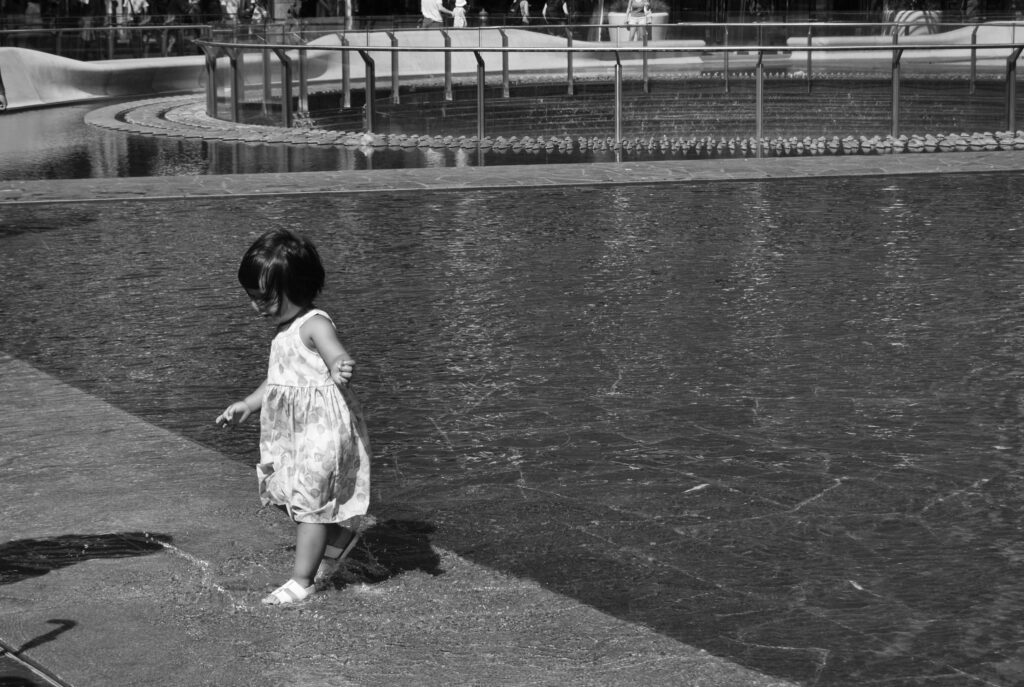 street photography black and white little girl in the water playing